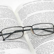Reading glasses with light frame over the open book — Stock Photo