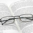Royalty-Free Stock Photo: Reading glasses with light frame over the open book
