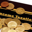 "Stock Photo: Book of ""Income Taxation"" and coins isolated on white"