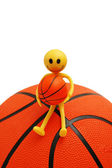 Smilie sitting on basketball isolated on white — Stock Photo
