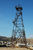 Old oil derrick during bright summer day — Stock Photo