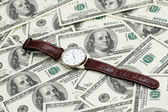 Hand watch over the hundred dollar bank notes — Stock Photo