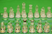 Glass chess figures against green background — Stock Photo