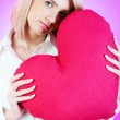 Romantic concept with girl and heart-shaped pillow — Stock Photo