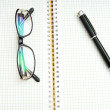 Pen and eye glasses on the page — Stock Photo #4419096