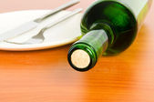 Bottle of wine on the wooden table — Stock Photo