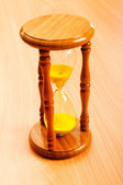 Time concept with hourglass on wooden background — Stock Photo