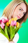 年轻女孩与背景色彩缤纷的郁金香 — 图库照片