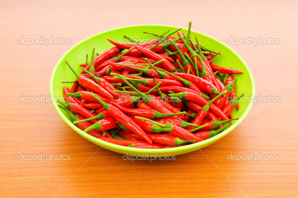 Hot peppers in the plate on wooden table — Stock Photo #4418306