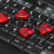 Love over the internet - red heart shapes on tje keyboard — Stock Photo