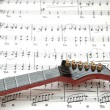 Stock Photo: Rock guitar over sheet of printed music