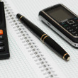 Calculator, ballpen and mobile phone on the notebook — Stock Photo #4425565