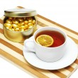 Cup of tea with lemon and chocolates isolated on white — Stock Photo #4426005