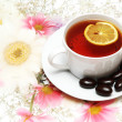 Tea with lemon and chocolates on floral background - Stock Photo
