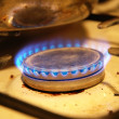 Blue flames from the dirty gas stove - Stock Photo