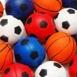 Selection of basketballs and footballs - Stock Photo
