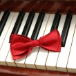 Red bow-tie on piano keys - Stock Photo