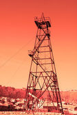 "Oil derrick with ""donkey"" pump during sunset — Stock Photo"