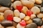 Pebbles at the background and red heart shapes — Stock Photo