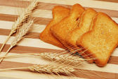 Four toast pieces and wheat ears on wooden board — Stock Photo