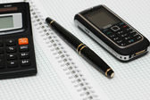Calculator, ballpen and mobile phone on the notebook — Stock Photo