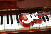 Guitar on the piano keys — Stock Photo