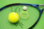 Tennis ball, shuttlecock and racket on green background — Stock Photo