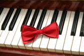 Red bow-tie on piano keys — Stock Photo