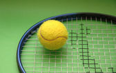 Tennis racket and ball on green background — Stock Photo