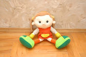Doll sitting on the wooden floor — Stock Photo