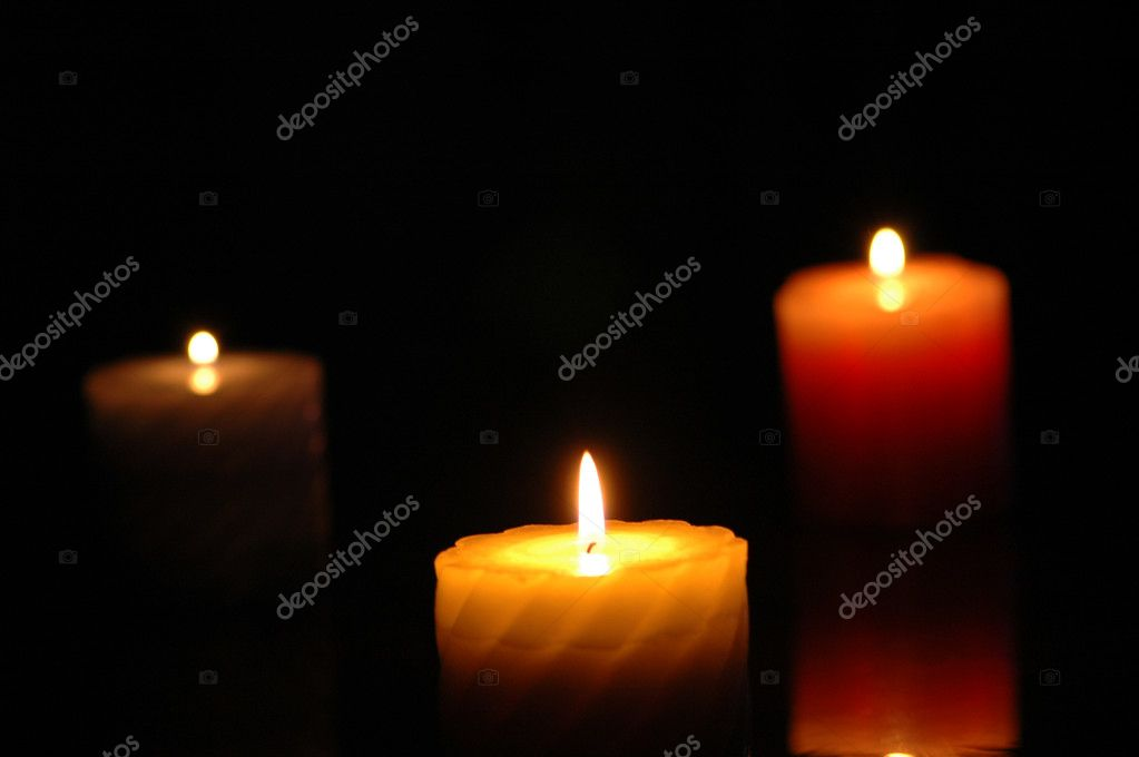 Three candles in the darkness - focus on the middle one — Lizenzfreies Foto #4424501