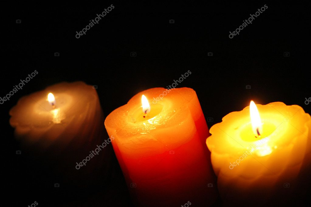 Three candles in the darkness - focus on the middle one — Stock Photo #4425923