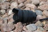 Camera lens on pebbles — Stock Photo