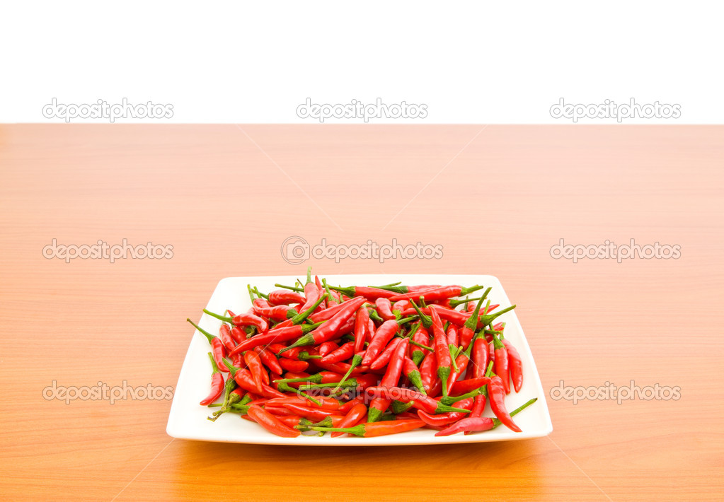 Hot peppers in the plate on wooden table — Stock Photo #4439158