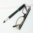 Pen and eye glasses on the page — Stock Photo