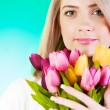 Young girl with tulips against colourful background — Stock Photo #4443765
