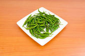 Hot peppers in the plate on wooden table — Stock Photo