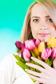 Young girl with tulips against colourful background — Stock Photo