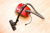 Vacuum cleaner on the wooden floor — Stock Photo