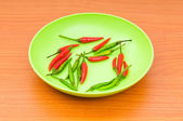 Hot peppers in the plate on wooden table — Stock fotografie