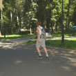 Girl on roller-blades skating across the park - Foto Stock