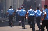 Policemen with batons running away — Stock Photo