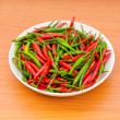 Hot peppers in the plate on wooden table — Stock Photo #4460762