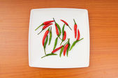 Hot peppers in the plate on wooden table — Stok fotoğraf