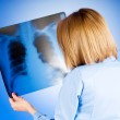 Female doctor carefully x-ray of patient — Stock Photo
