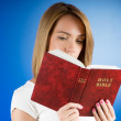 Royalty-Free Stock Photo: Religion concept - Young girl reading holy bible