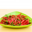 Hot peppers in the plate on wooden table — Stock Photo #4510815