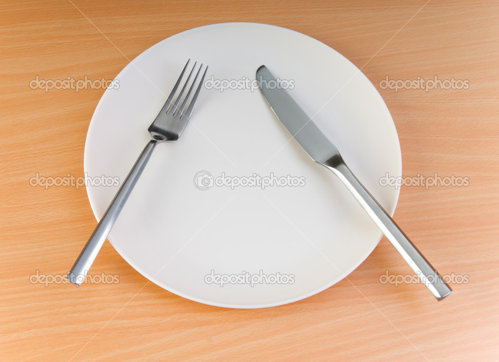 Plate with utensils on wooden table stock photo elnur for Table utensils