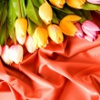 Many flowers on the red satin background — Stock Photo #4529652