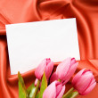 Envelope and flowers on the satin background — Stock Photo